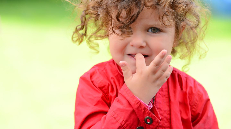 Fingernägelkauen bei Kindern: Kleines Mädchen knabbert am Nagel ihres Zeigefingers.